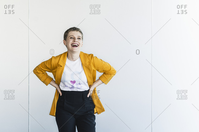 Cheerful businesswoman wearing yellow blazer with hands on hip standing against wall in office