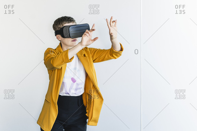 Businesswoman looking through virtual reality simulator while standing against wall in office