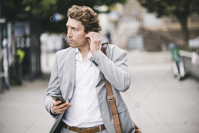 Man adjusting in-ear headphones while standing at sidewalk in city