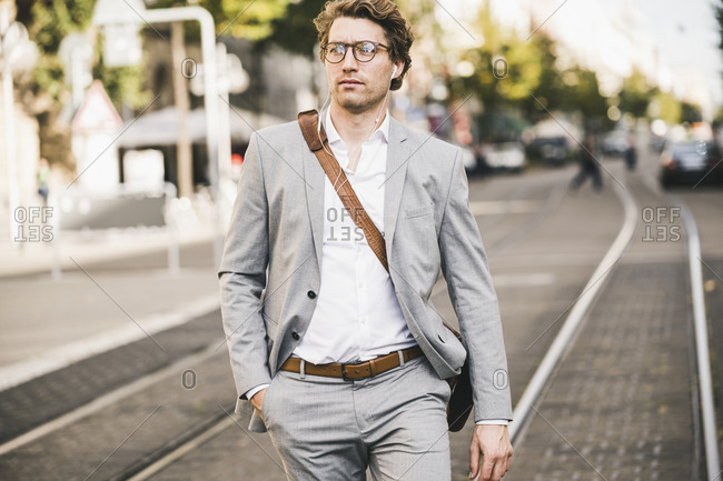 Handsome man with hands in pockets walking on tramway in city