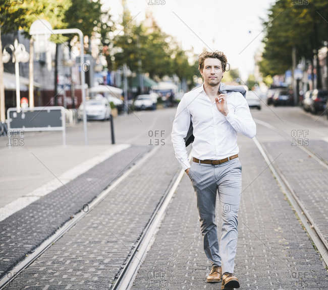 Businessman walking with hand in pocket and jacket over shoulder in city