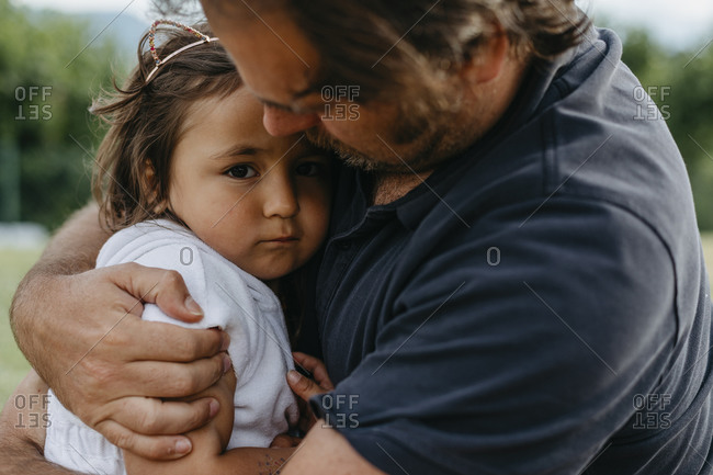 Father embracing daughter while sitting at backyard