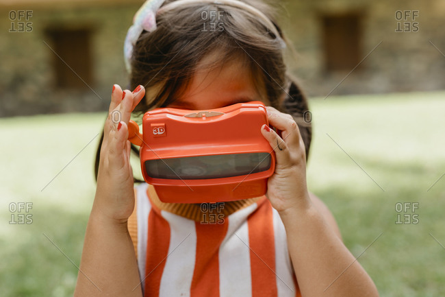 Girl playing with virtual reality toy while standing at back yard