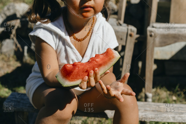 Girl eating watermelon while sitting on log