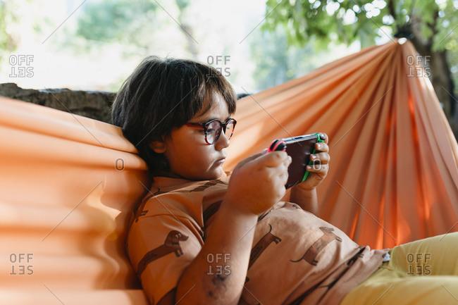 Boy wearing eyeglasses playing handheld video game