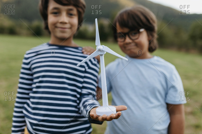 Smiling boys holding windmill toy while standing at backyard