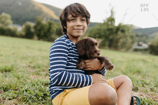 Boy holding puppy while sitting on grass at backyard