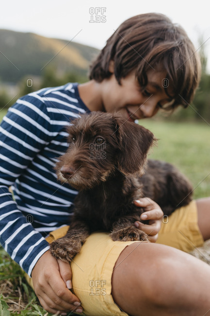 Smiling boy playing with puppy while sitting on grass at backyard