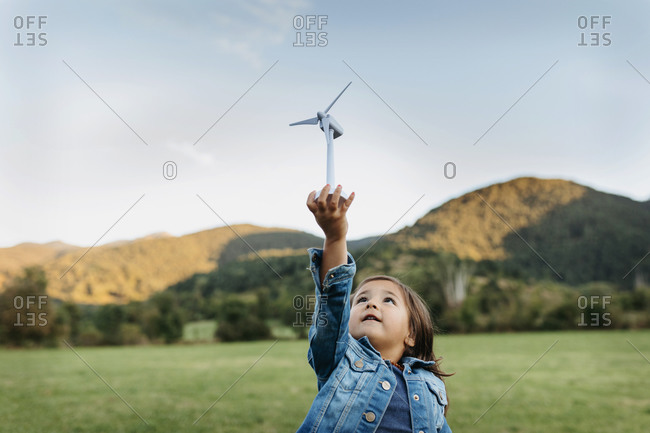 Cute girl playing with wind turbine toy while standing at backyard