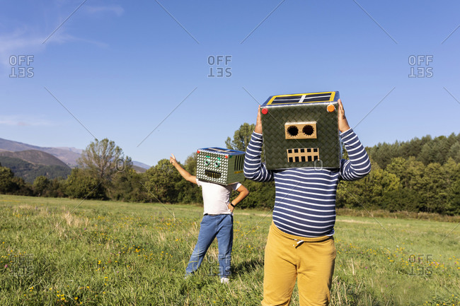 Brothers enjoying playing with robot and smiling cardboard box in meadow