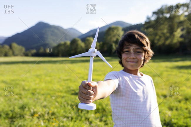 Smiling boy holding wind turbine toy while standing in meadow
