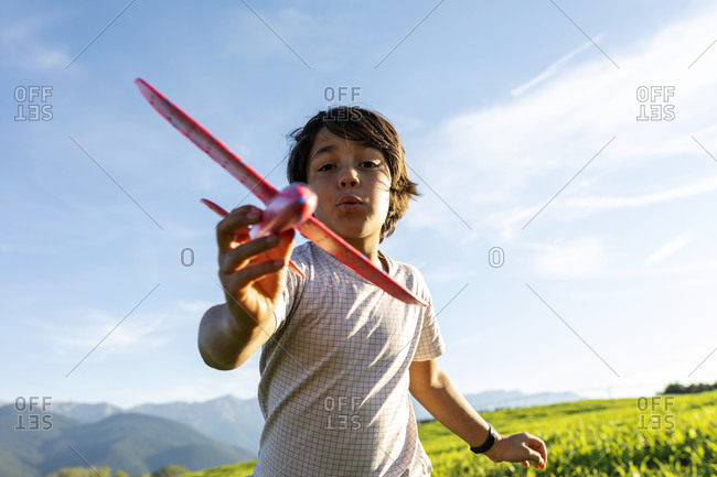 Boy playing with airplane toy while standing against clear sky