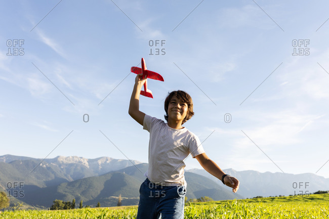 Smiling boy holding airplane toy while standing against clear sky