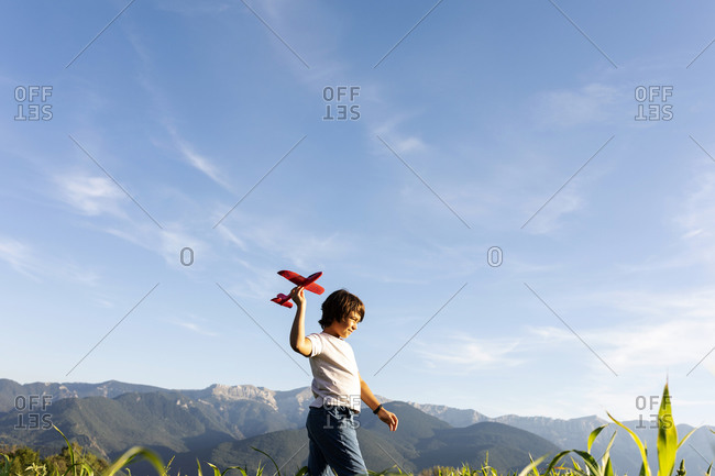 Boy holding airplane toy while walking against clear sky