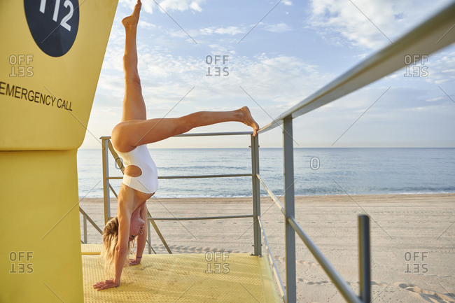 Woman practicing handstand exercise at lifeguard hut on beach