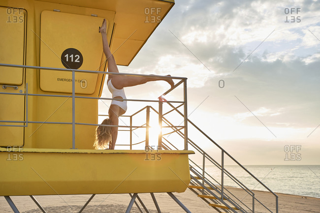 Woman practicing handstand yoga at lifeguard hut on beach