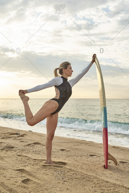Woman stretching leg while leaning on surfboard at beach