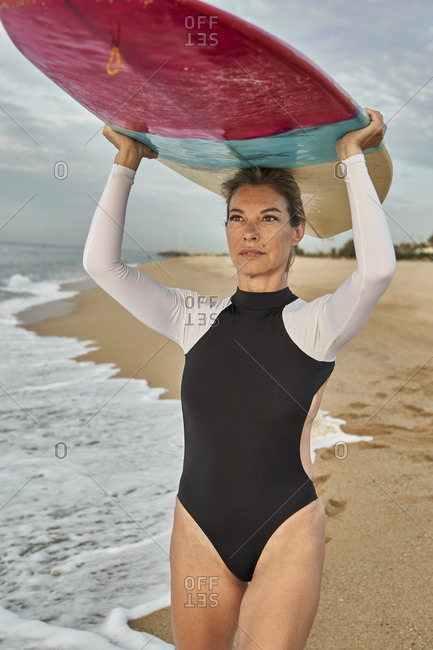 Beautiful woman carrying surfboard on head while standing at beach