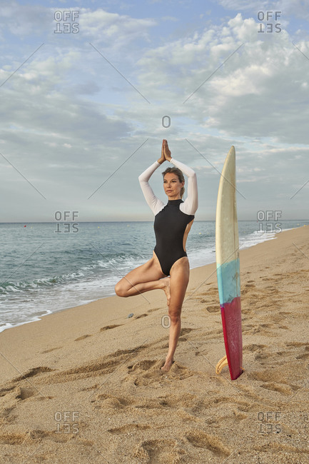 Woman practicing yoga while standing by surfboard at beach