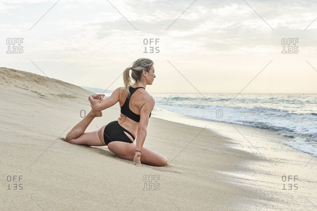 Woman doing yoga while sitting by water's edge at beach