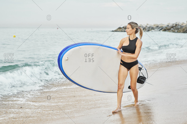Woman carrying surfboard looking away while walking at beach