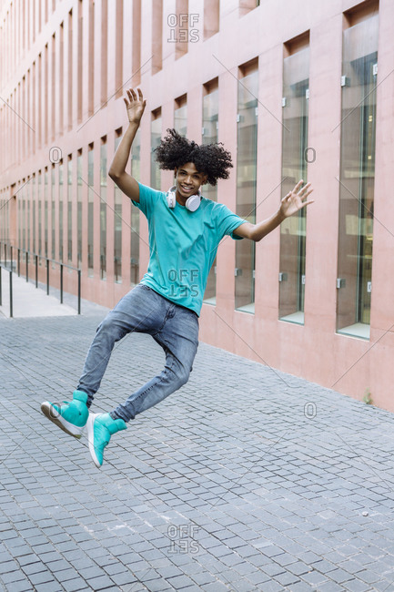 Young man jumping on street in city