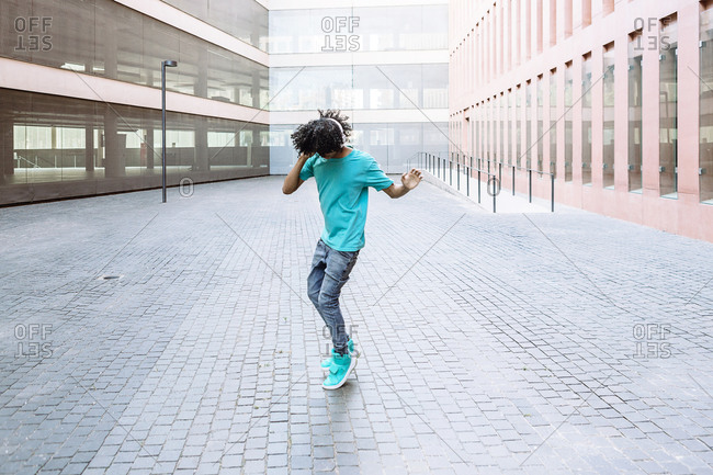 Young man listening music while dancing on street in city