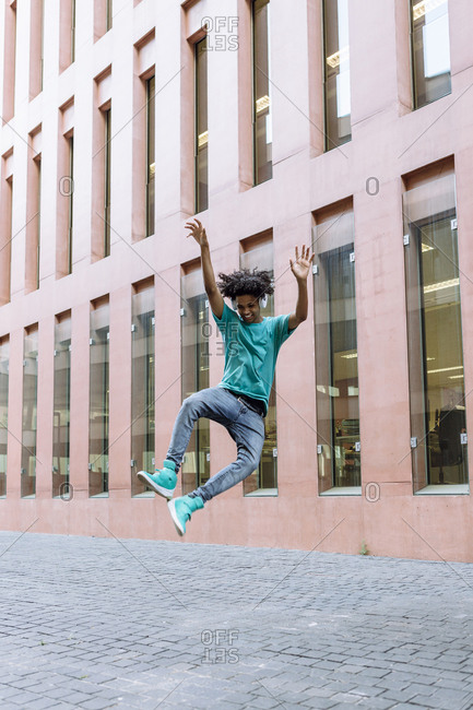 Young man jumping with hand raised on street in city