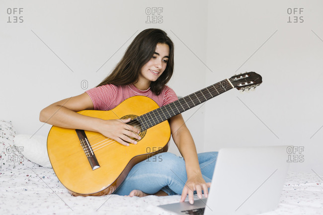 Woman learning guitar online at home in bedroom