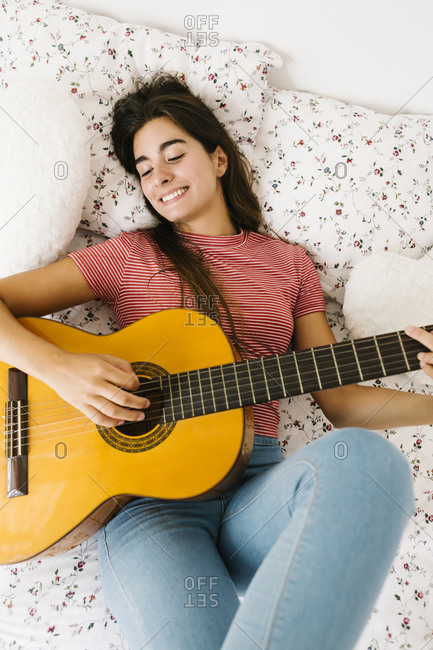 Young woman lying on back while playing guitar in bedroom