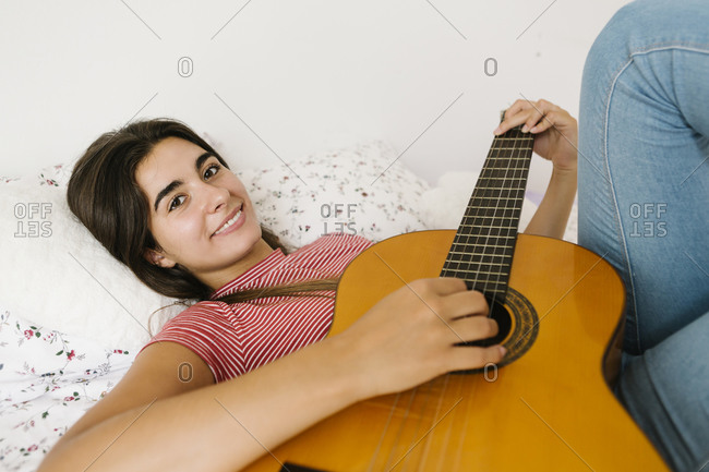 Young woman lying down while playing guitar in bedroom