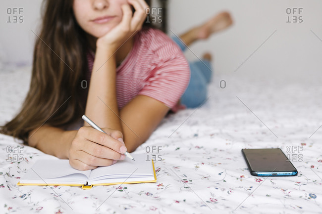 Woman taking notes in book while lying down on bed at home