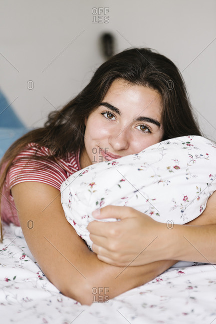 Smiling woman with pillow lying on bed at home in bedroom
