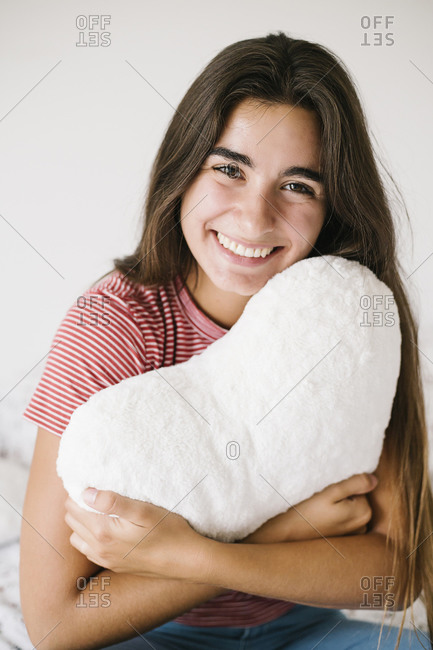 Smiling young woman with heart shape pillow sitting in room at home