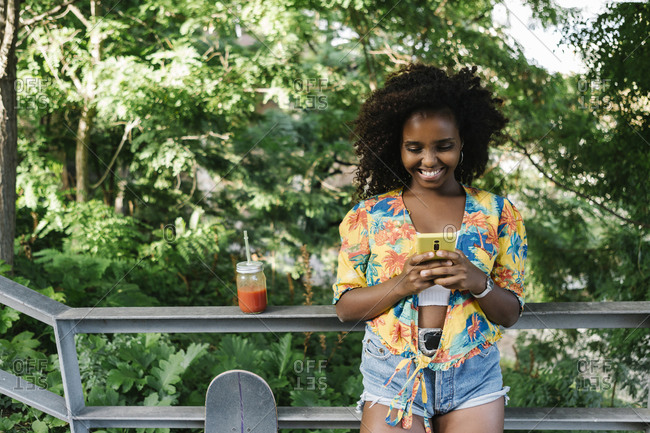 Smiling woman text messaging on smart phone standing against railing in park