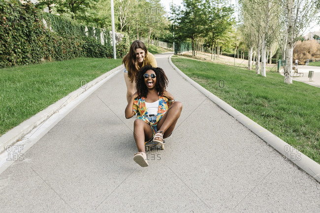 Young woman pushing her friend sitting on skateboard in park