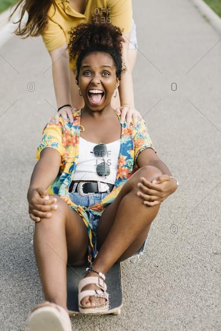 Woman pushing her friend sitting on skateboard in park