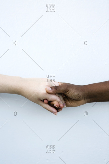 Friends shaking hand against white wall