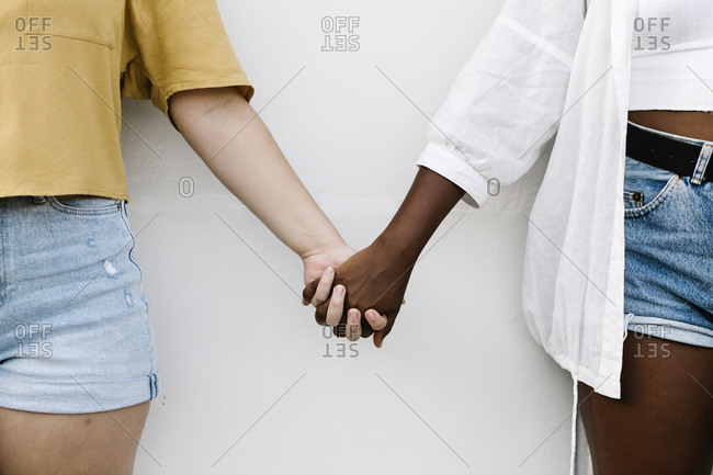 Friends holding hand while standing against white wall