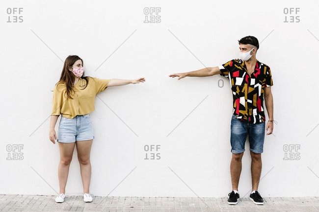 Young friends keeping social distancing while standing against wall