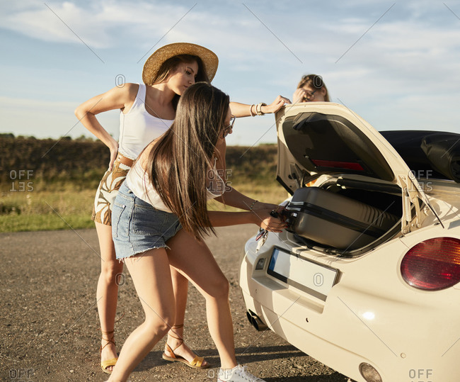 Female friends removing suitcase from car trunk