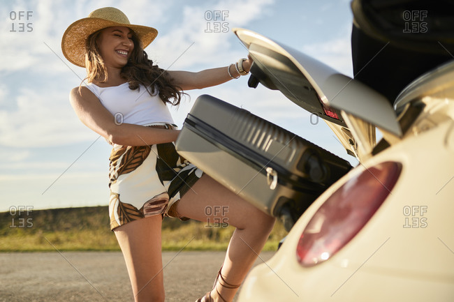 Smiling young woman removing suitcase from car trunk