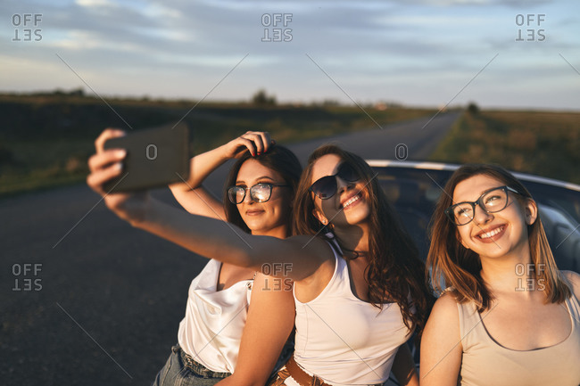 Smiling friends taking selfie while standing on road during sunset