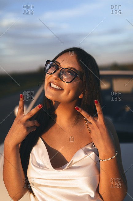 Beautiful woman smiling while doing hand gesture during sunset
