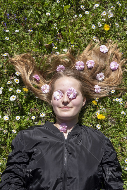 Girl lies in a flower meadow with daisies on her eyes and cherry blossoms in her hair