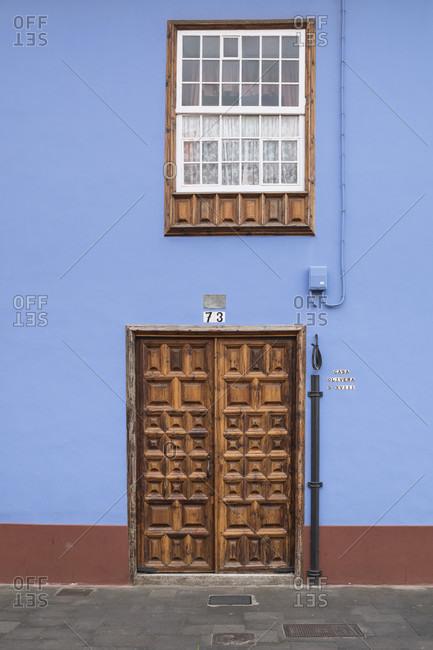 Blue apartment building with wooden entrance door with ornaments on Calle san Agustina, san Cristóbal de la laguna, tenerife, canary islands, Spain