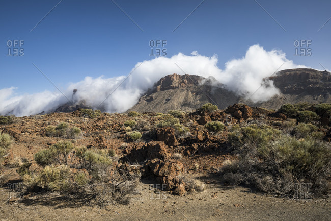 Cloud waterfall over the calderarand mountains in the el teide national park, unesco world heritage, tenerife, canary islands, Spain
