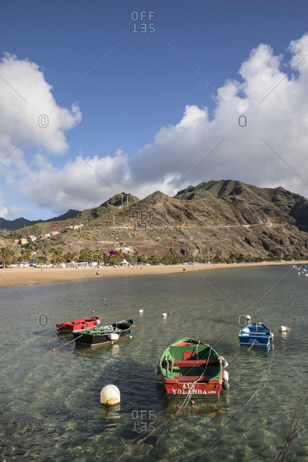 January 25, 2020: colorful fishing boats in front of the playa de las teresitas beach and the anaga mountains, san Andres, tenerife, canary islands, Spain