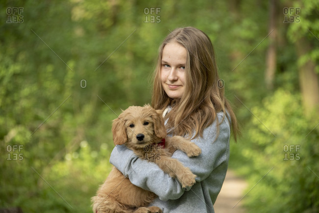 Girl on a forest walk with a dog, mini goldendoodle