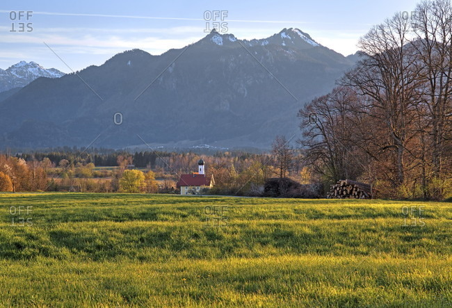 Spring landscape with little church from the hamlet of weichs against ettaler mandl (1633m) and labor (1686m) of the ammergau alps, ohlstadt, das blaue land, upper Bavaria, Bavaria, Germany